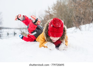 Two little girls in bright winter clothes and red hats among the winter landscape. One girl in a yellow jacket is lying on her stomach in the snow, the second is lying with her legs up behind