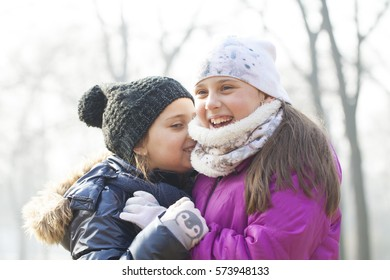 Two little girls with caps and scarves play