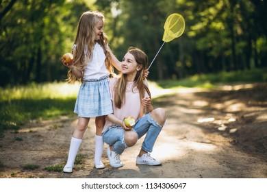 Two little girls catching butterflies