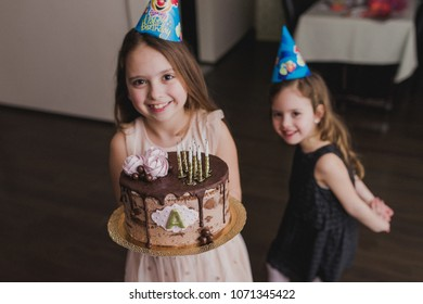 Two little girls celebrating birthday, holding a cake