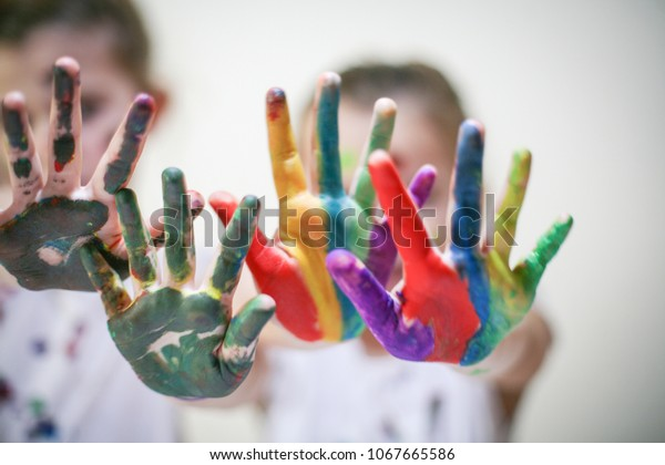 Two little girls with colored hands. Close up. Focus on hands.