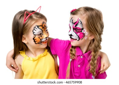 two little girls with colorful painted faces looking at each other