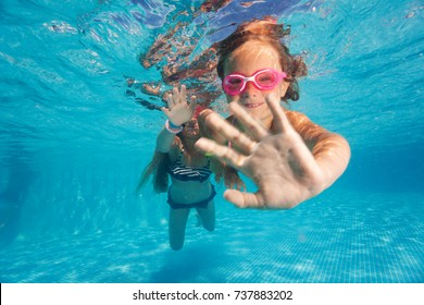 Two little girls diving underwater in pool