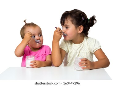two little girls eating yogurt isolated on white