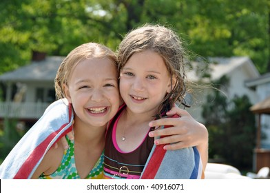 two little girls embrace after swimming on a summer day