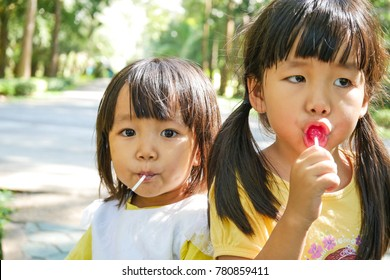 The two little girls are enjoy eating their lollipops.