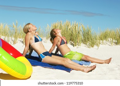 Two little girls enjoy in sunbathing on sandy beach