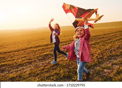 Two little girls friends have fun together with kite and toy plane on the field at sunny daytime.