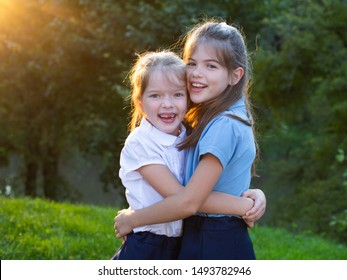 Two little girls friends in school uniform hug each other in the park.