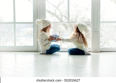 two little girls friends or sisters with long blond hair in white hats and white cardigans and jeans sitting near the window and playing with gift at winter time at winter time