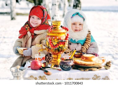 two little girls in fur coats and shawls in Russian style . The celebration of Shrovetide in Russia.