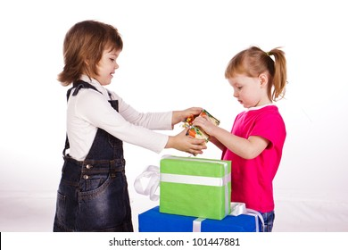 Two little girls with gift boxes isolated on white