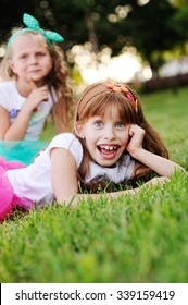 two little girls grimace on the grass background