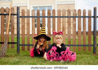 Two little girls in halloween gowns sitting on green lawn by wooden fence