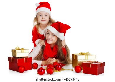 Two little girls in hats of Santa Claus lying down with gifts. White background