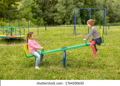 Two little girls have fun on a swing outdoors