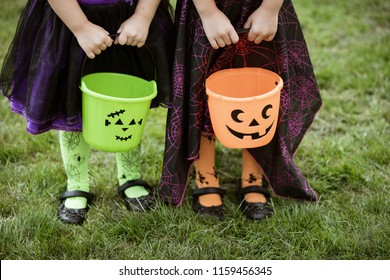 Two little girls hold an orange and green jack o lantern trick or treat candy buckets