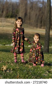 Two little girls holding hands at the park