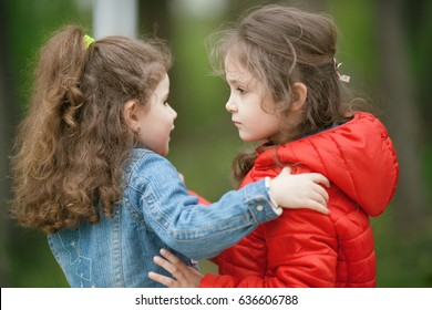 Two little girls hug and play