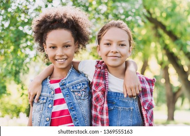 Two little girls hugging in the park. Kids friends playing together outdoor. Summer fun, vacations concept