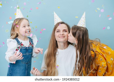 Two little girls hugging their mother on a cheek, all in party cones over blue background. Mother put her hands over daughters'.