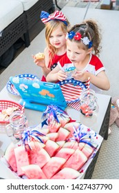 Two little girls in July 4th outfits are eating cupcakes and watching tablet on the back patio.