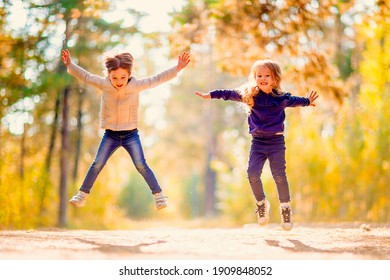 Two little girls jumping and having fun together outdoors