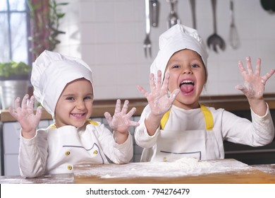 Two little girls in the kitchen prepare food, a dessert for the family. As they learn to cook they start playing with flour and smiling each other. Concept of: cooking classes, family, education.