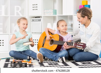 Two little girls learning to play musical instruments guided by a smiling teacher