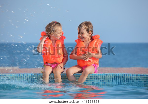 two little girls in life-jackets sitting on ledge pool on resort, Looking against each other