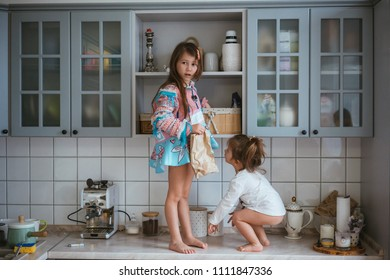 two little girls are looking for cookies in the kitchen