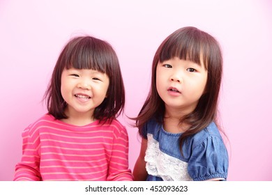 two little girls looking front together,Asian