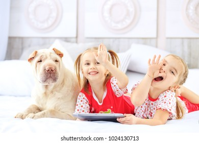 Two little girls lying on the bed with a tablet. Dog. The concept of childhood, lifestyle, game.
