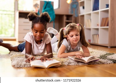 Two little girls lying on the playroom floor, reading books for school, studying. Focus on the girl on the right