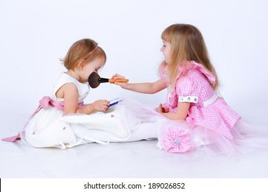 Two little girls with a makeup brush and a small mirror in studio