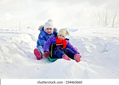 Two little girls on a sled in the snow in the winter