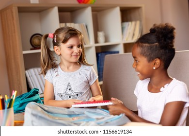 Two little girls packing their school bags, getting ready for the first day of school