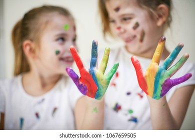 Two little girls with paint on face and hands. Close up.