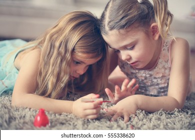 Two little girls painted their nails at home.