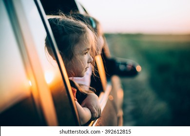 Two little girls peeks out of the car in the sunset