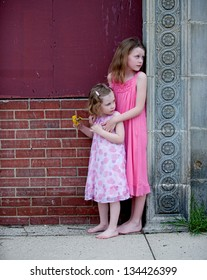 Two little girls with pink dresses standing next to wall, looking back anxiously