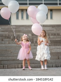 Two little girls in pink and white dressses with balloons walking on the street in city