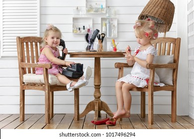 Two little girls play in the beauty salon on the home terrace