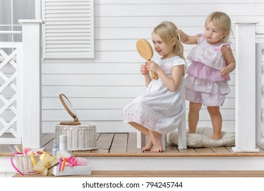 Two little girls play in the beauty salon on at home on the porch