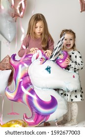 Two little girls play with a big unicorn balloon surrounded by balloons on a white background