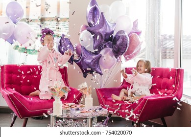 Two little girls play with conffeti sitting in large pink sofa surrounded with balloons