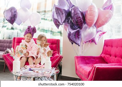 Two little girls play with cookies sitting in large pink sofa surrounded with balloons