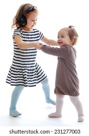 Two little girls play holding hands.Isolated on white background.