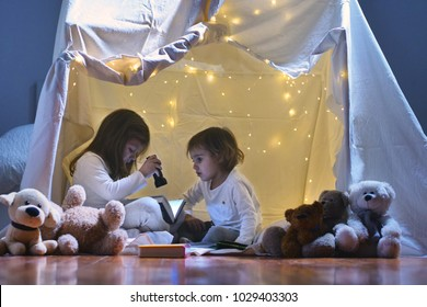 Two little girls play at home in the evening to build a camping tent to read books with a flashlight and sleep inside. Concept of: game, magic, creativity, alarm systems