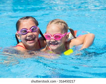 Two little girls play and swim in the pool